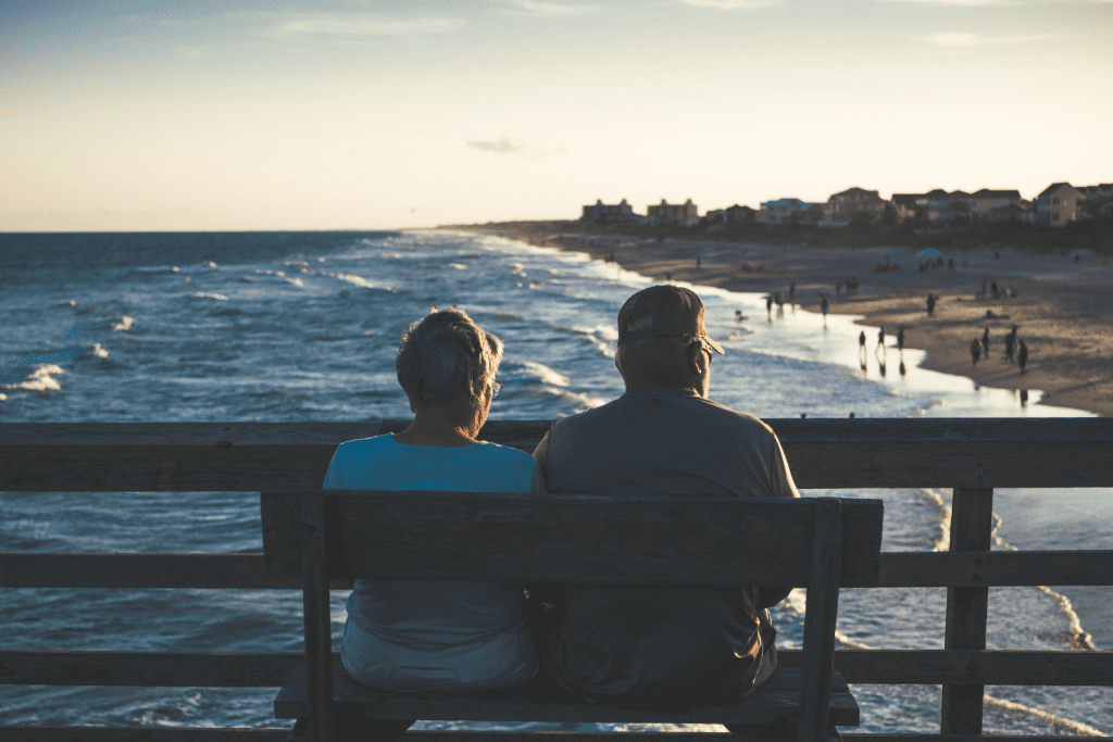 a couple sitting on a bench near the ocean
