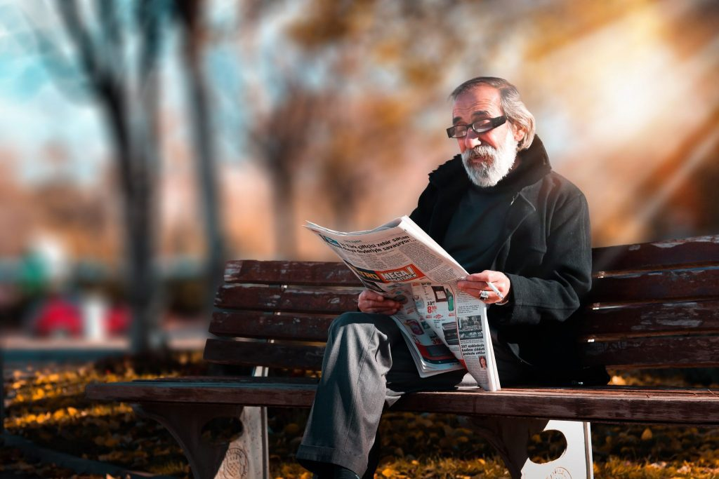 man on bench reading a newspaper